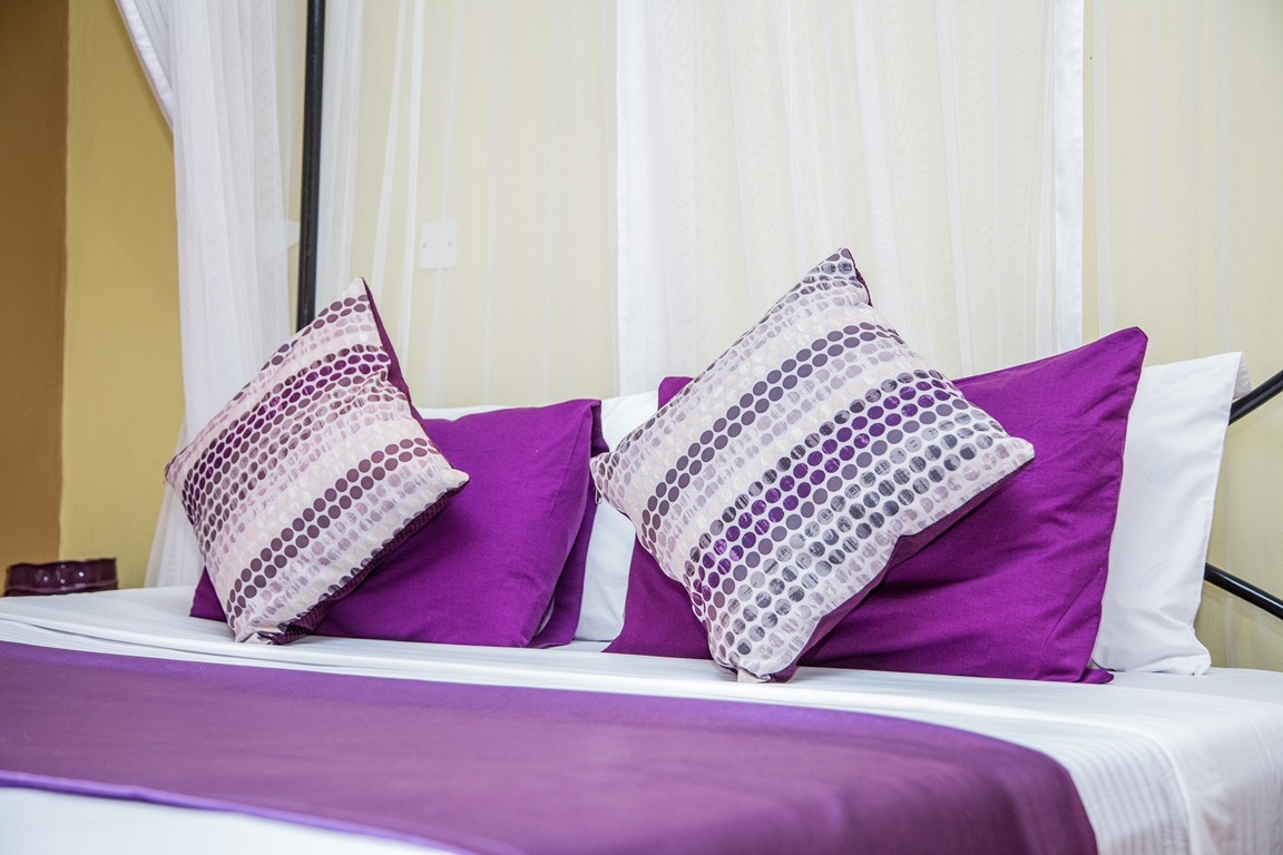 A king size bed inside one of the superior rooms at Adonai Guesthouse in Muyenga, Kampala