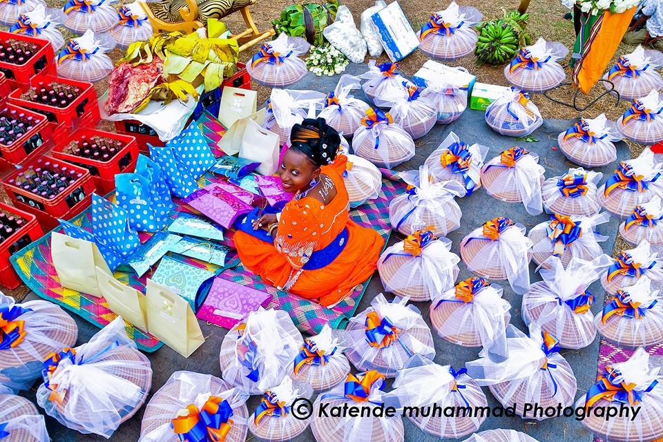 A bride in a red gomesi surrounded by gifts at an introduction