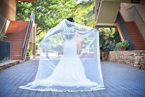 Liz shows off her long veil during a wedding photo at Speke Resort Munyonyo