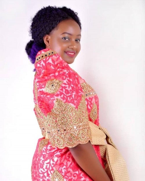 Dhalin Sandra clad in a red and gold gomesi from Kushona Designs