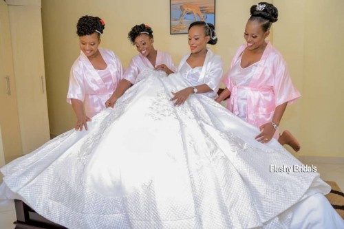 Bride shows off her wedding dress from Flashy Bridals to her maids