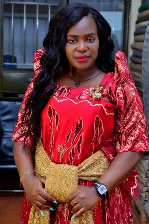 The Dance N' Beats Cultural Troupe director clad in a red and gold gomesi