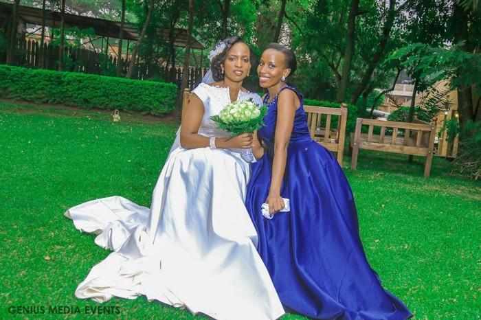 A bride & maid of honor in a royal blue dress covered by Genius Media Events