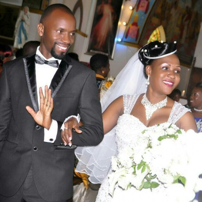 A bride and groom walk in church on their wedding day in Kampala