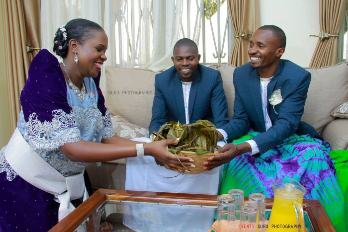 A bride to be passing over a luwombo to her spouse at a Kukyala