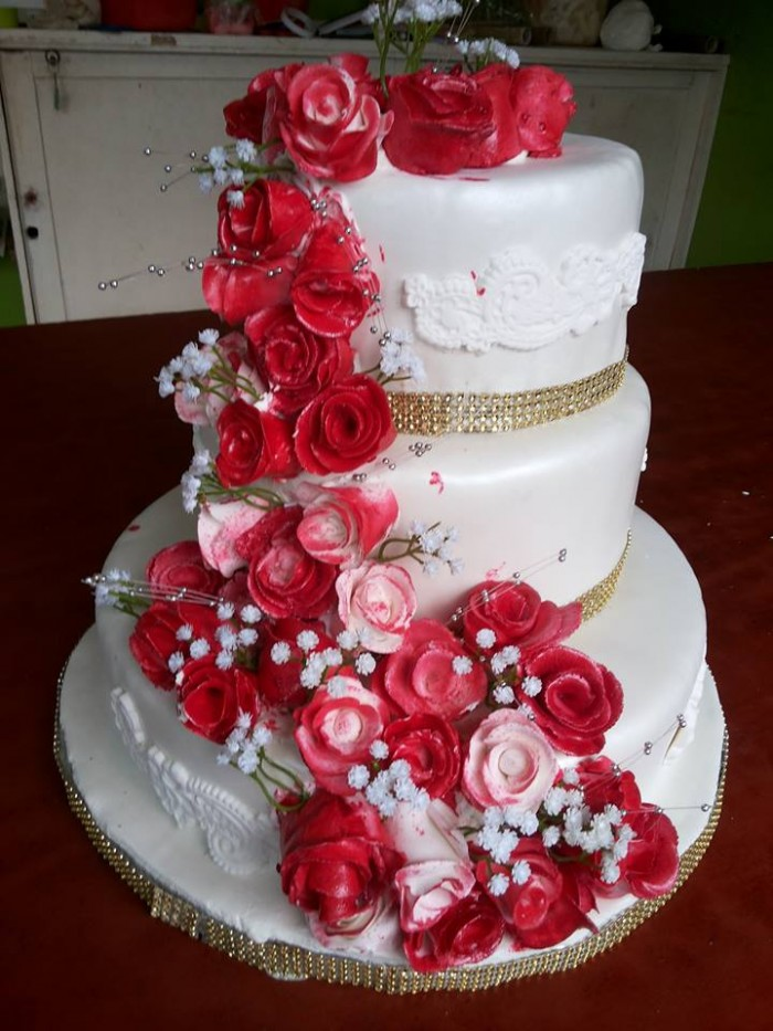 A white wedding cake decorated with red flowers and golden ribbon balls, baked by NHK Home Bakery