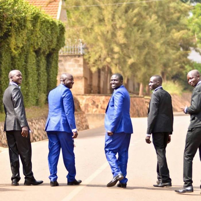 Groomsmen pose during street wedding photo shoot by Lenz Media