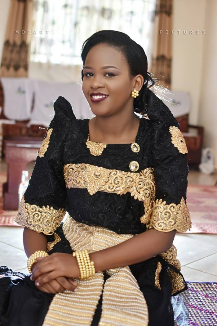 Beautiful lady in a black gomesi with a gold sash, customary wedding moments powered by Mozart pictures
