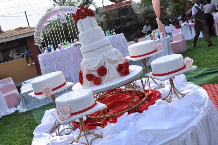 A white wedding cake decorated with red ribbons and flowers from Jari Events & Confectionary