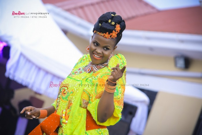 A bride dazzles in a yellow gomesi and a red sash at a customary wedding