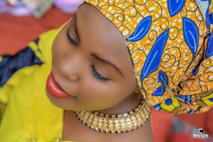 A bride with beautiful makeup and a kitengi head wrap captured by Watson Photography