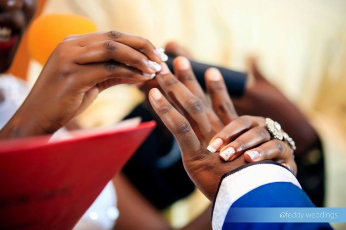 A bride putting a ring on the groom's finger in church