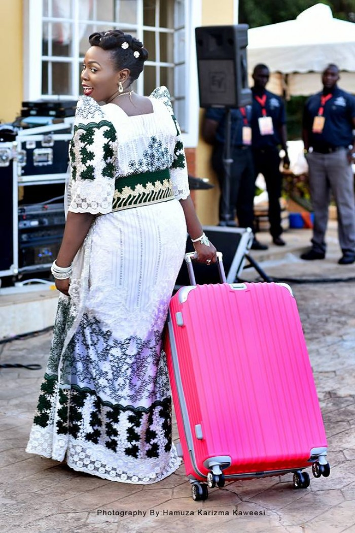 A bride strolls away with a suitcase during an introduction powered by Hamuza Karizma Kaweesi