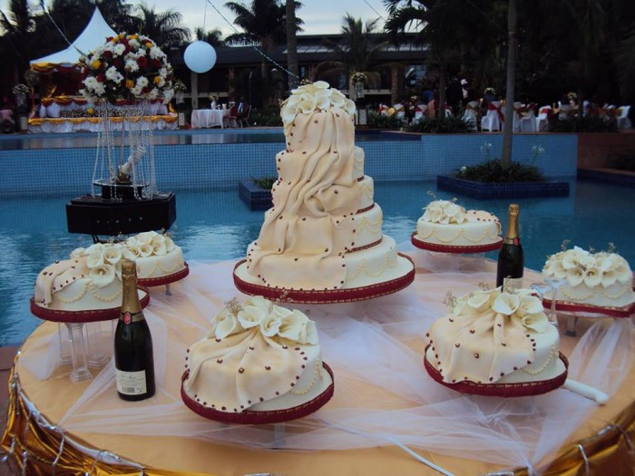 A nice wedding cake on a table at the swimming pool venue at Speke Resort Munyonyo