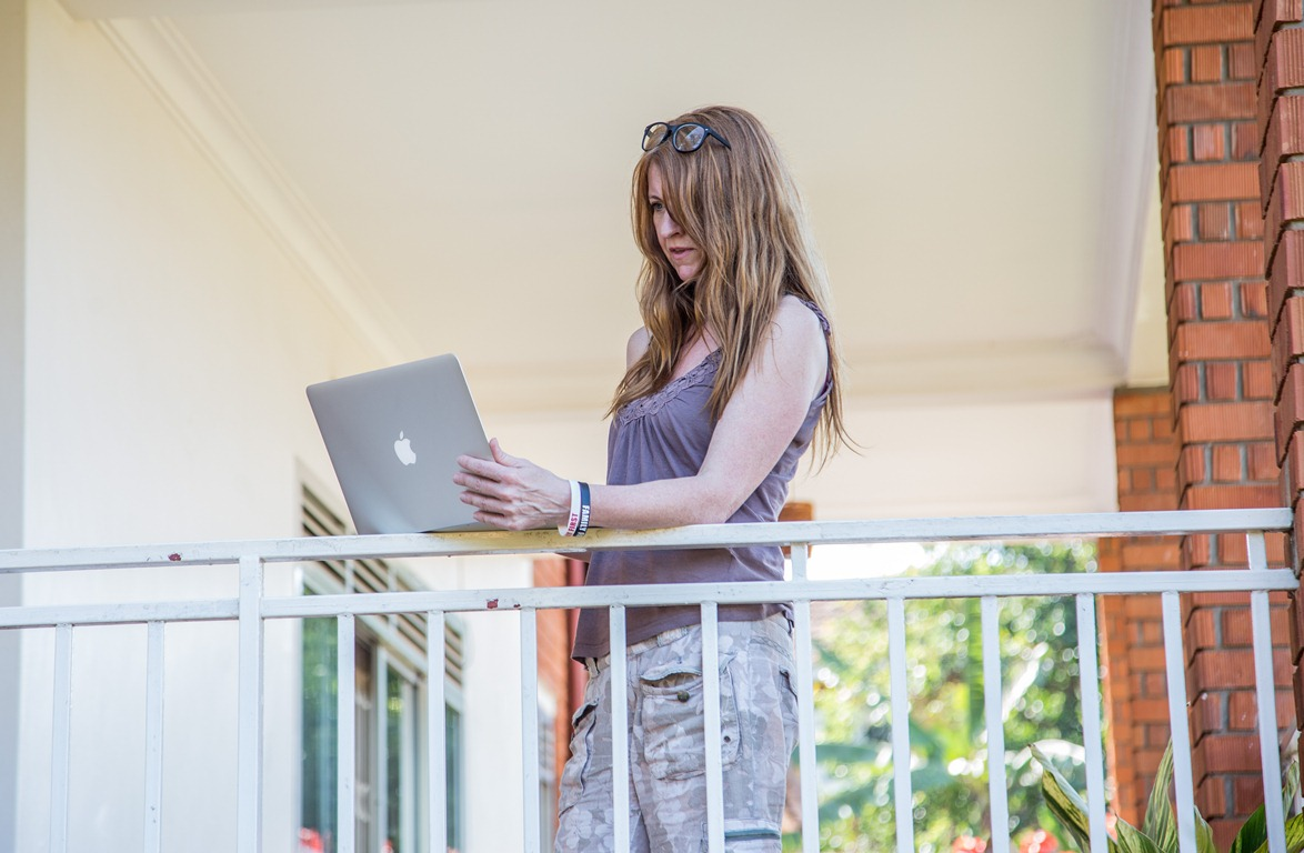 A guest browses the Internet on her computer at Adonai Guesthouse in Muyenga